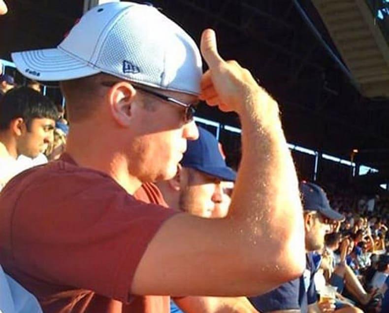Un hombre se protege del sol con la mano a la vez que viste una gorra con la visera hacia detrás.