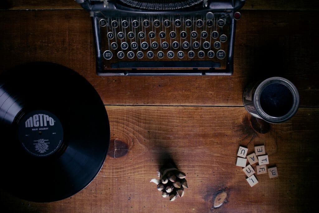 Máquina de escribir, disco de vinilo y unas piezas (letras) de scrabble.