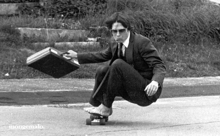 Un tipo con traje, maletín y descalzo, monta en un monopatín.