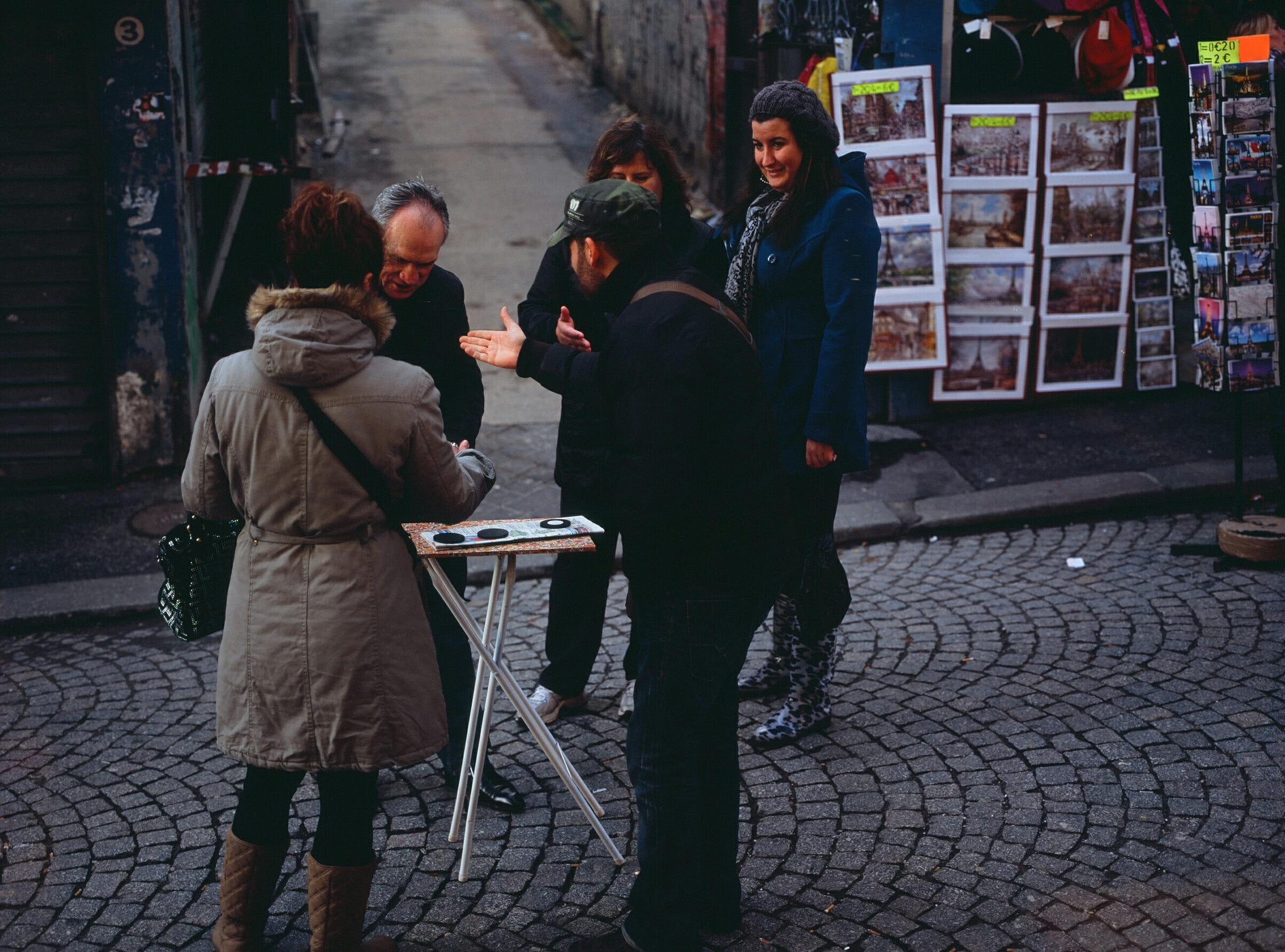 Tres mujeres y un hombre alrededor de un trilero en la calle.